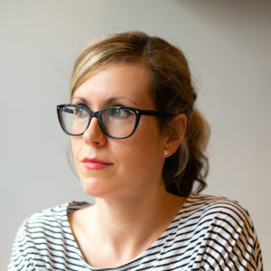 Photo of Vik, with light brown hair in a ponytail, big blue glasses and a black and white stripy top looking to her right