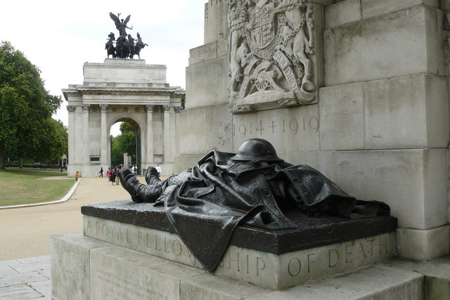 Photo of a WWI memorial in Hyde Park, London, with Marble Arch in the background. A statue of a soldier lying down, a helmet laid on his stomach.