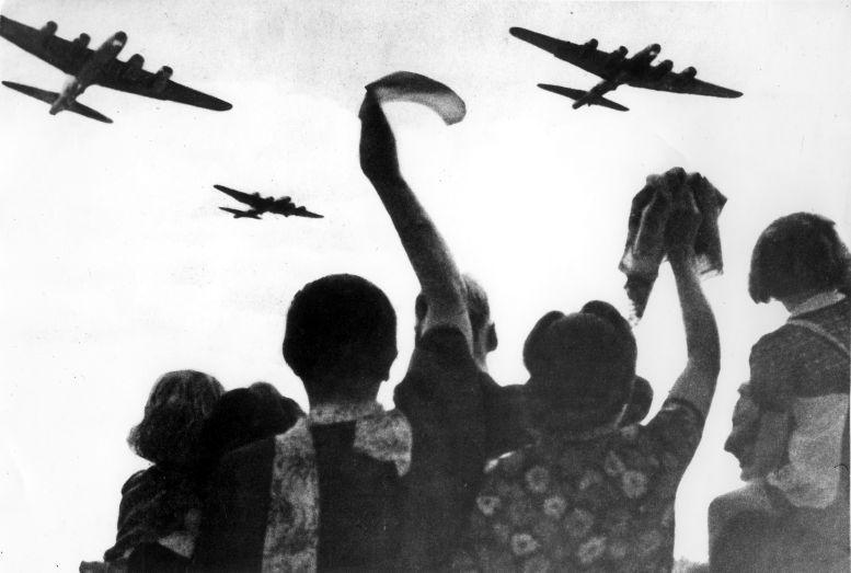 Tweede Wereldoorlog . Geallieerde vliegtuigen boven Nederland bij bevrijding. Zwaaiende mensen.