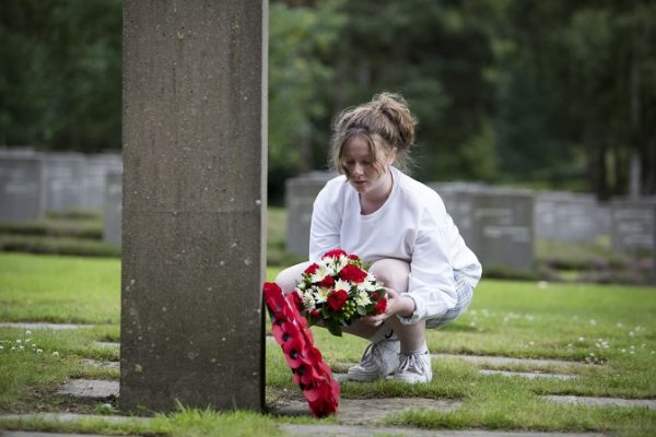 A young person laying a wreath to signify remembrance at the German War Graves in Cannock Chase.