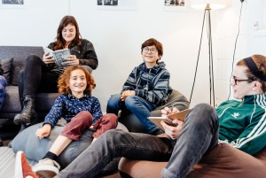 Four young writers sitting on a sofa and grinning with notebooks