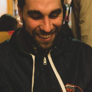 image of adam levin smiling and looking down