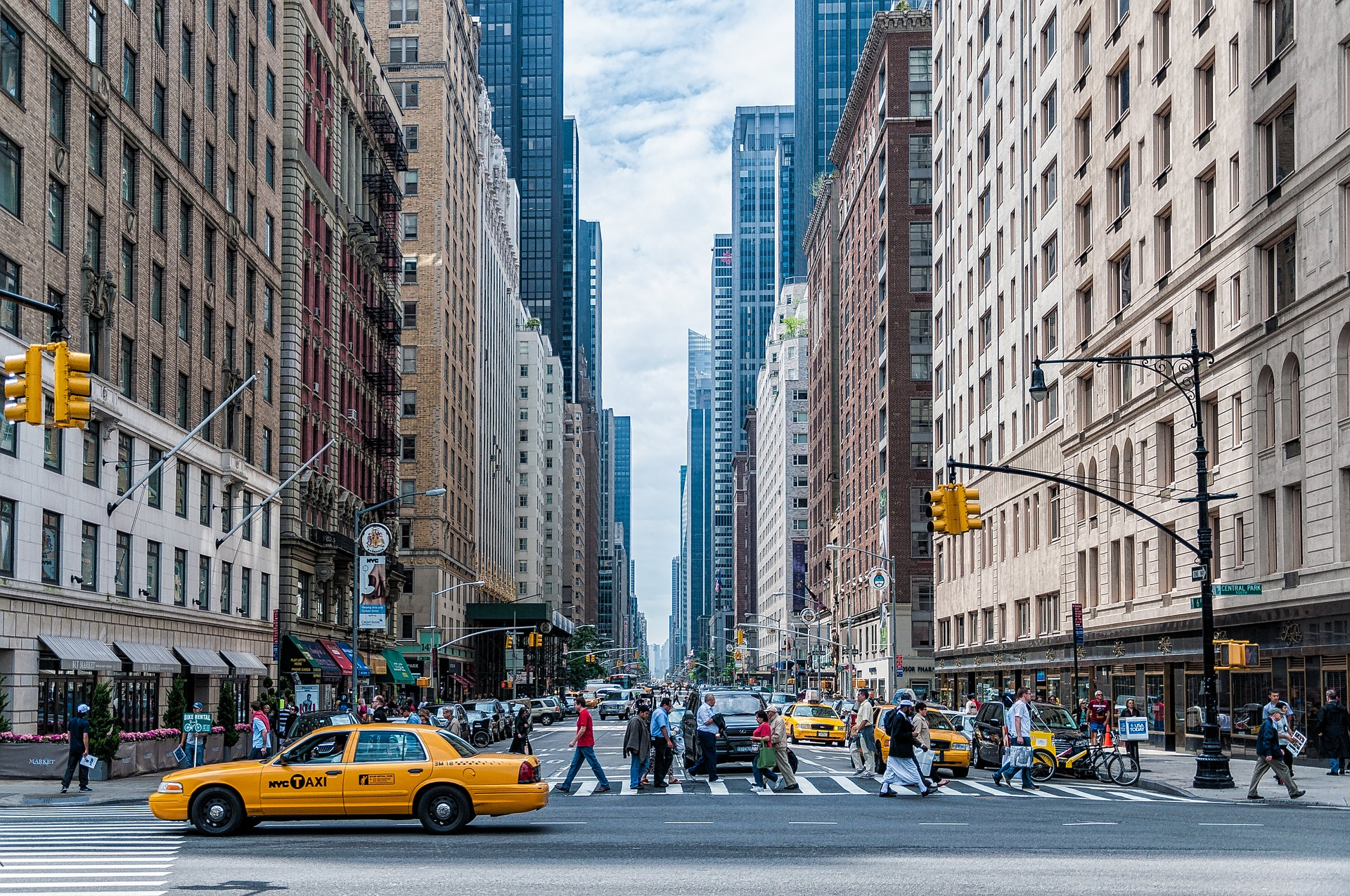 Photo of a street in New York. A yellow taxi cab in the foreground, people crossing the street at a crossing, tall buildings to the left and right of the photo.