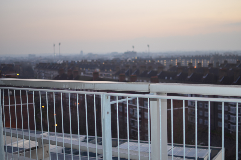 View of a white balcony looking over a city at dawn or dusk