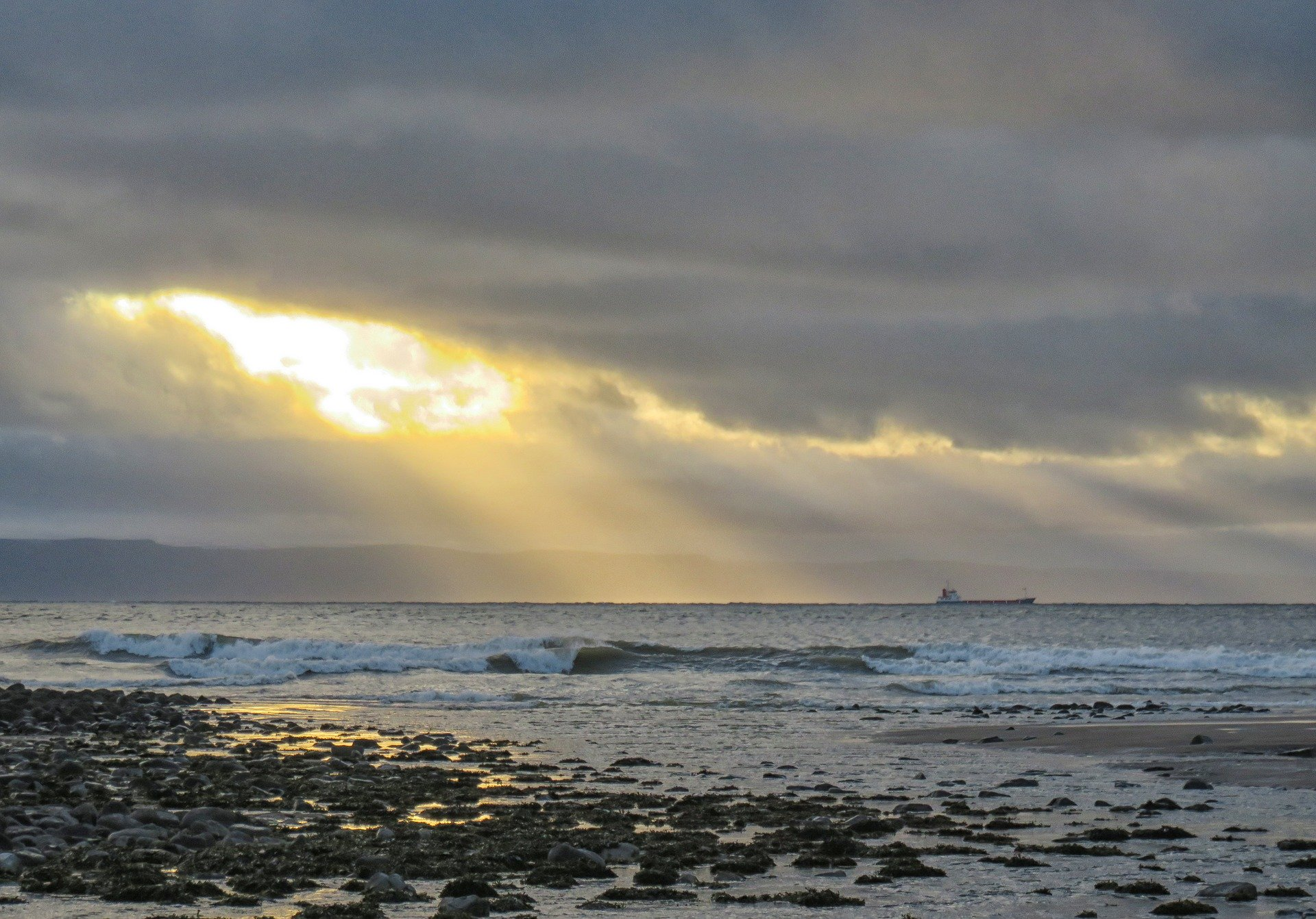 Photo of the English Channel: the sun streaks throguh a cloud