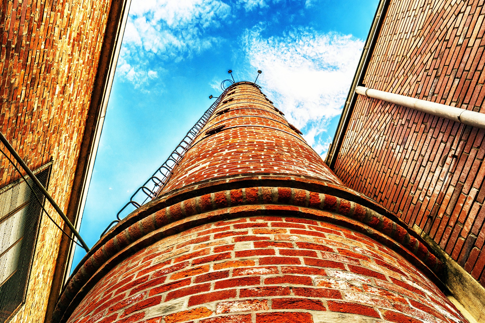 Chimney reaching up to a blue sky, seen from below