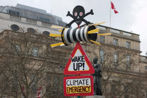 Photo of an adapted road sign in London which has a skull and crossbones on top, and in a red triangle says 'WAKE UP!' Below it another red box reads 'CLIMATE EMERGENCY'.