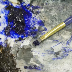 Photo of a paintbrush and some dark blue and black paint