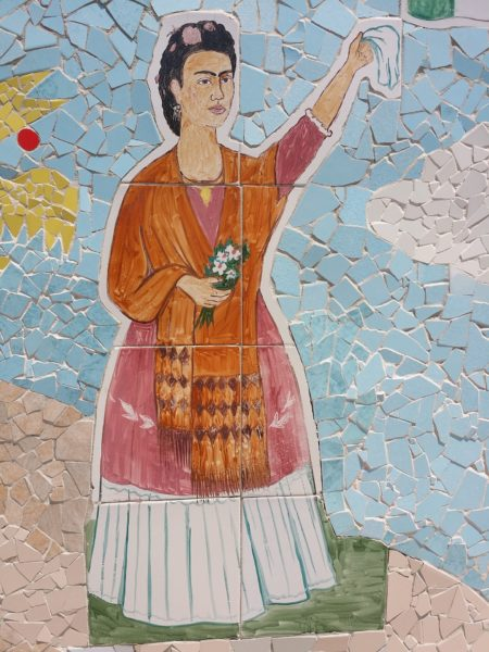 Frida Kahlo mural painted onto a wall: she waers a long dress and holds one hand up holding a handkerchief, and in the other hand a small bouquet of flowers