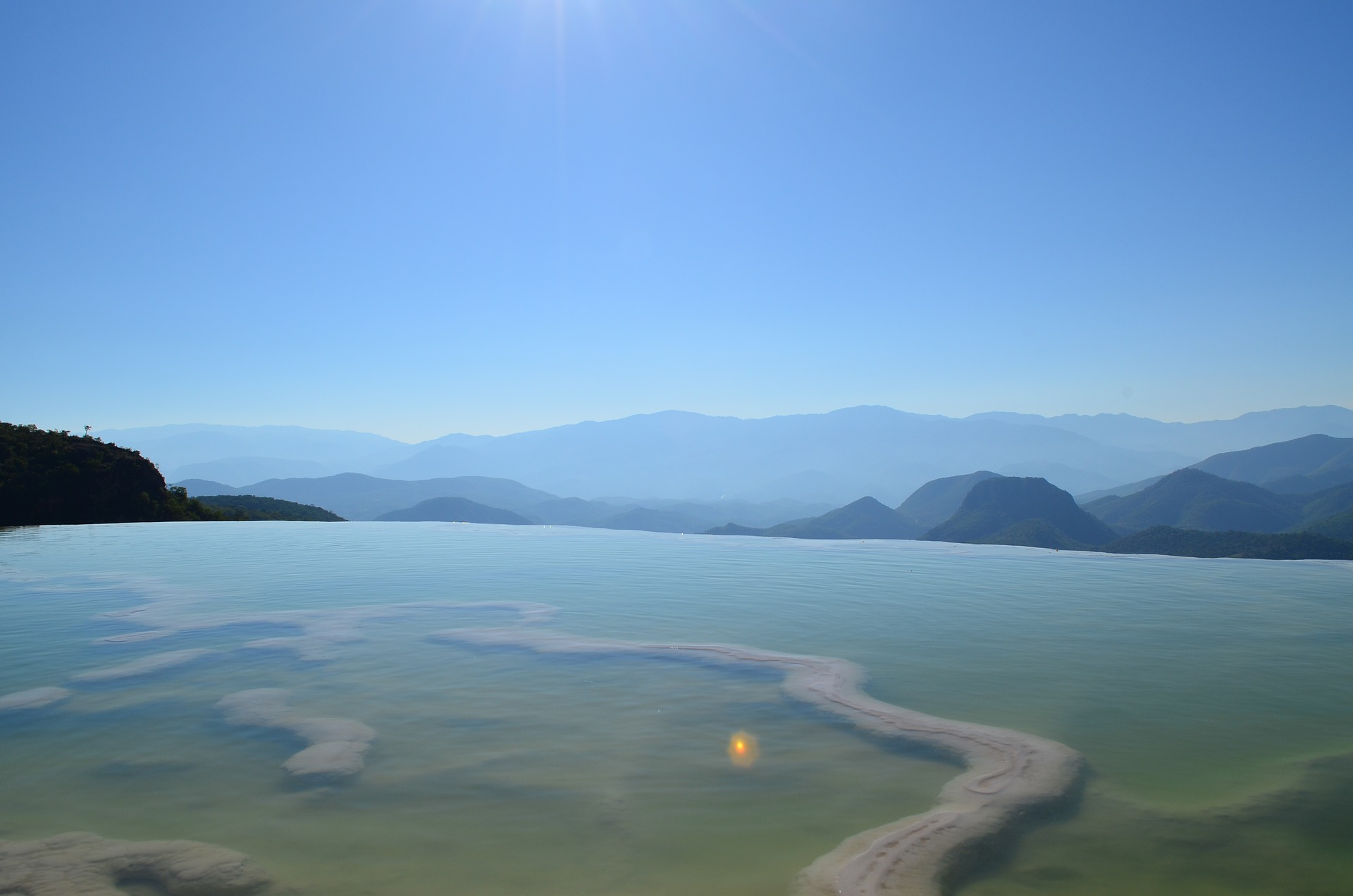 Blue sky and mountains in the distance; what appears to be still water in the foreground