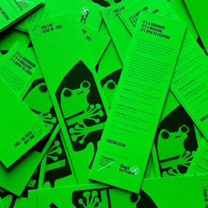dozens of a green bookmark-shaped magazine with an illustration of a frog on the front cover cover the surface