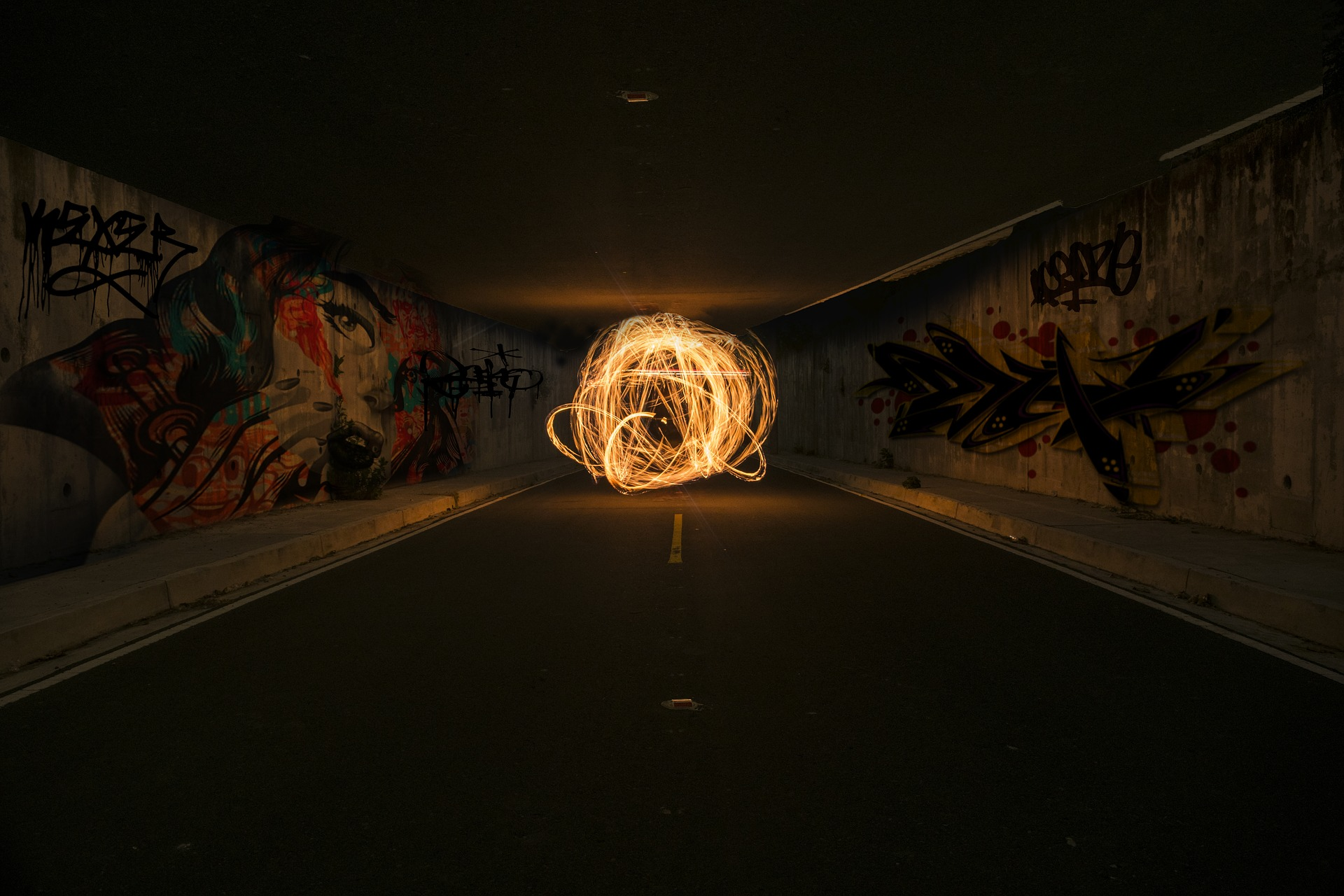 Photo of a ball of light in a dark tunnel whose walls are covered in graffiti