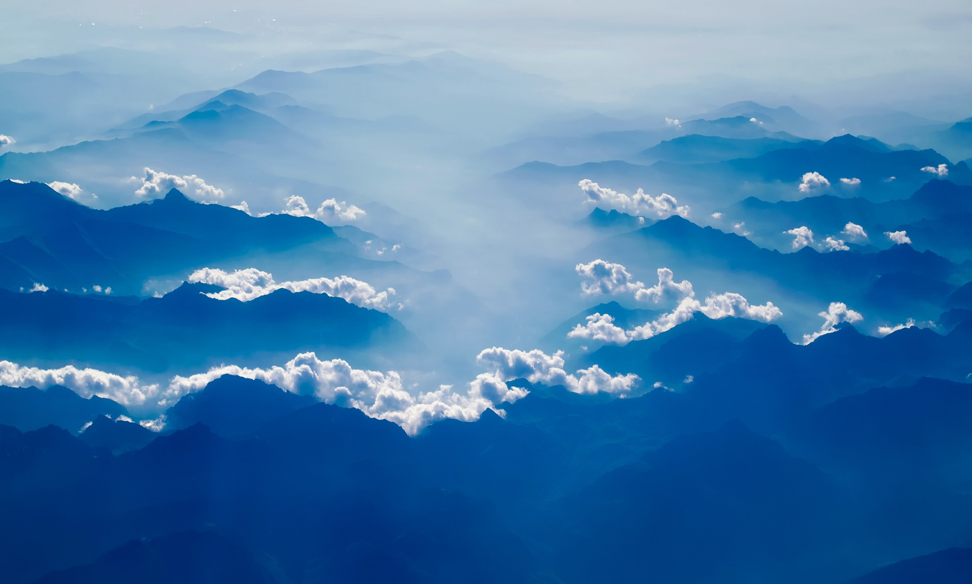 photo of blue mountains peeking through clouds