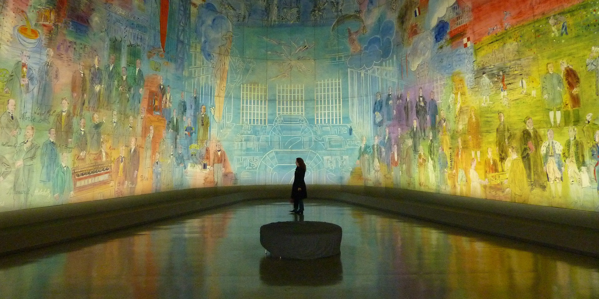 woman stands in a museum surrounded by wall-to-wall art