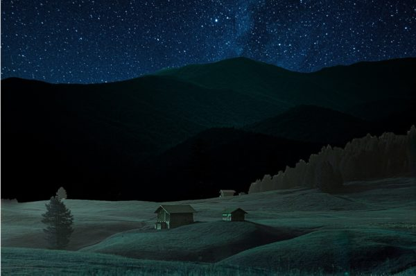 Night time photo of a house by a mountain