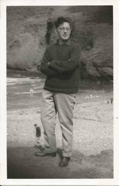 Charles Causley stands, arms crossed, on the beach in a black and white photo