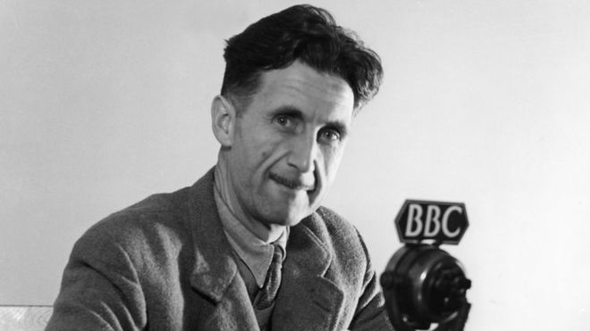 Black and white photo of George Orwell sitting in front of a microphone labelled BBC