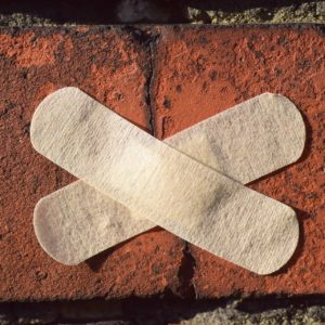 Photo of a brick with two plasters stuck to it in the shape of an X