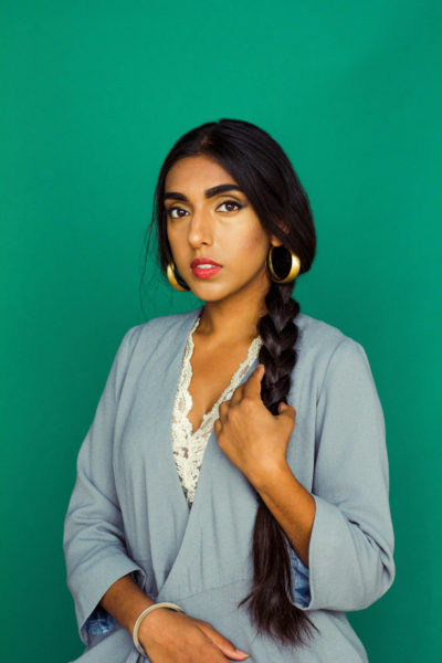Rupi Kaur holds her long plaited hair