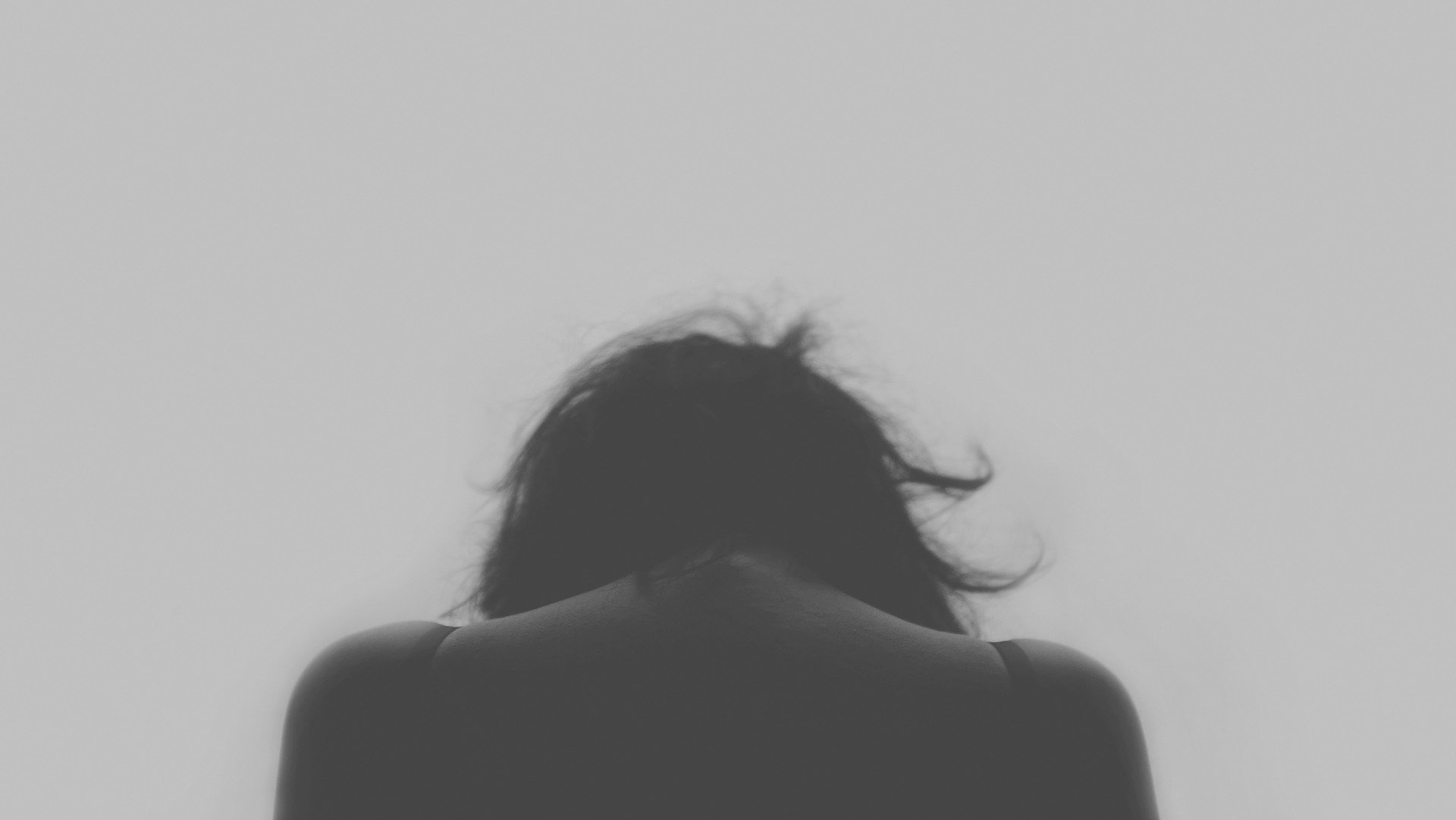 Black and white photo of a woman's head and shoulders from behind; she is looking down as if in pain