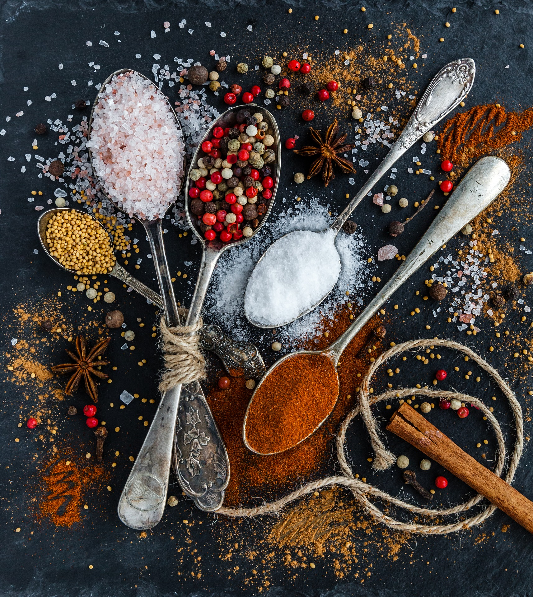 Image of four spoons, heaped with different ingredients: cinnamon, salt, and two other colourful condiments