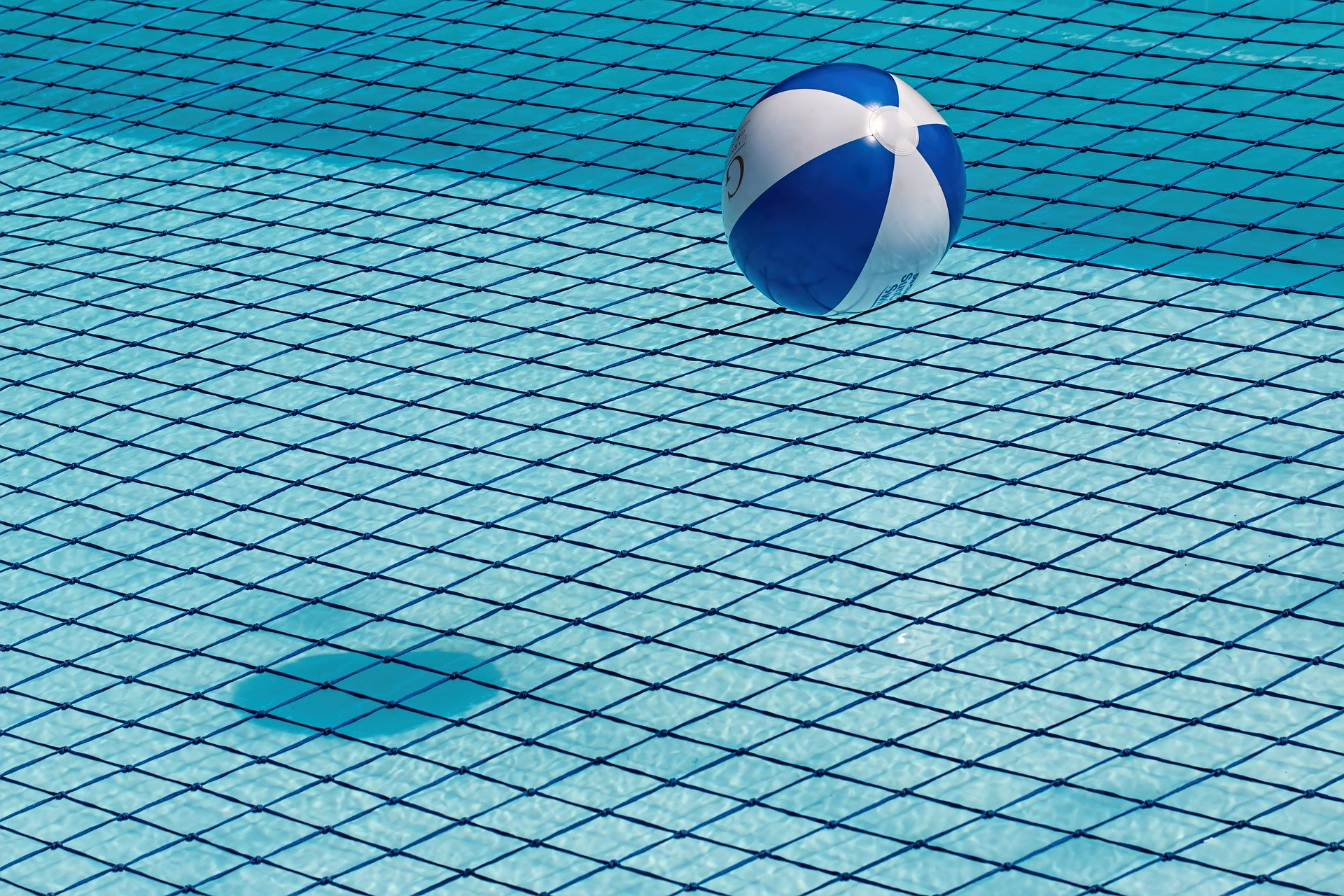 Photo of a blue and white beach ball resting on a black safety net above a blue outdoor pool
