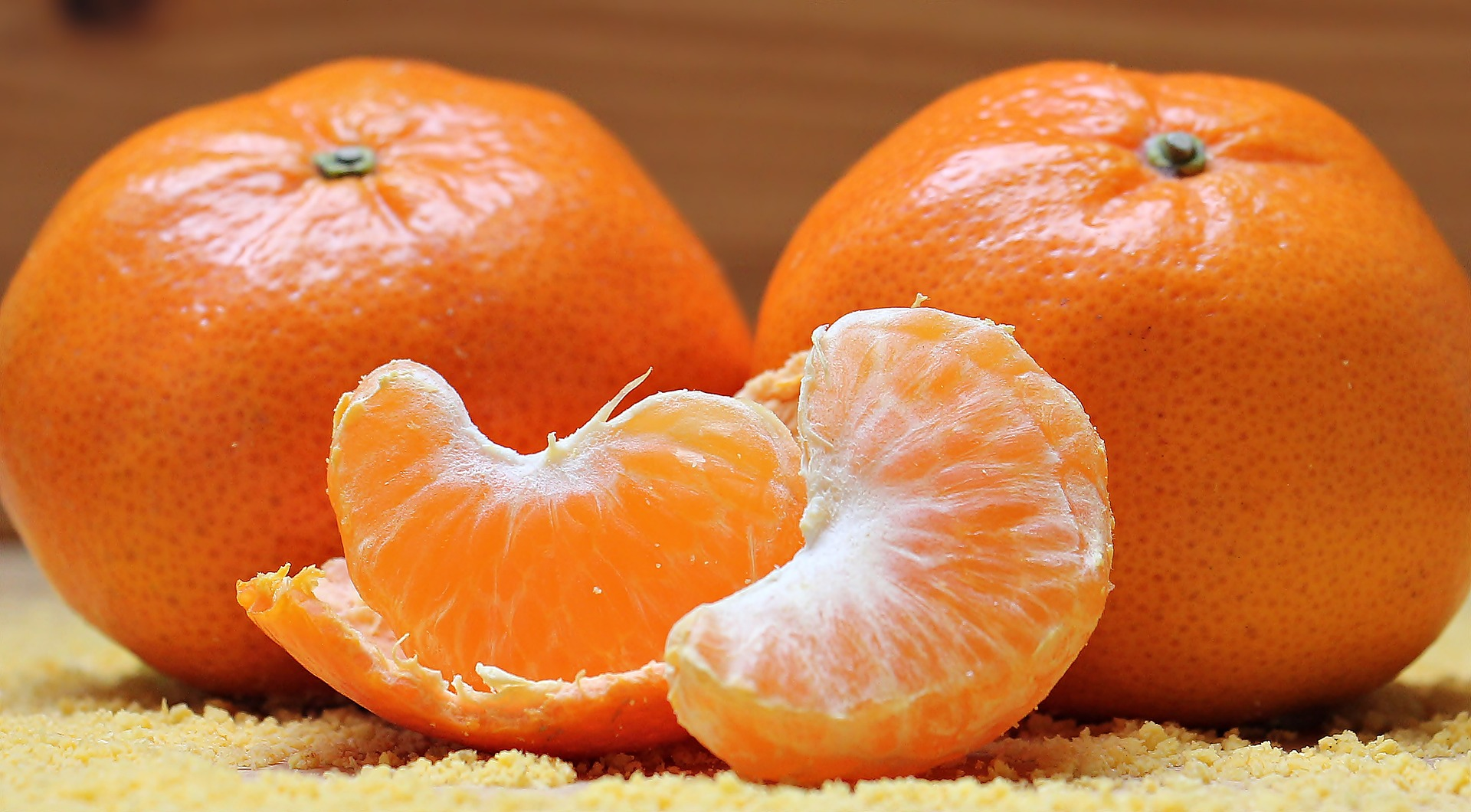 Close-up photo of two tangerines side-by-side, and two segments of a tangerine in the middle of them